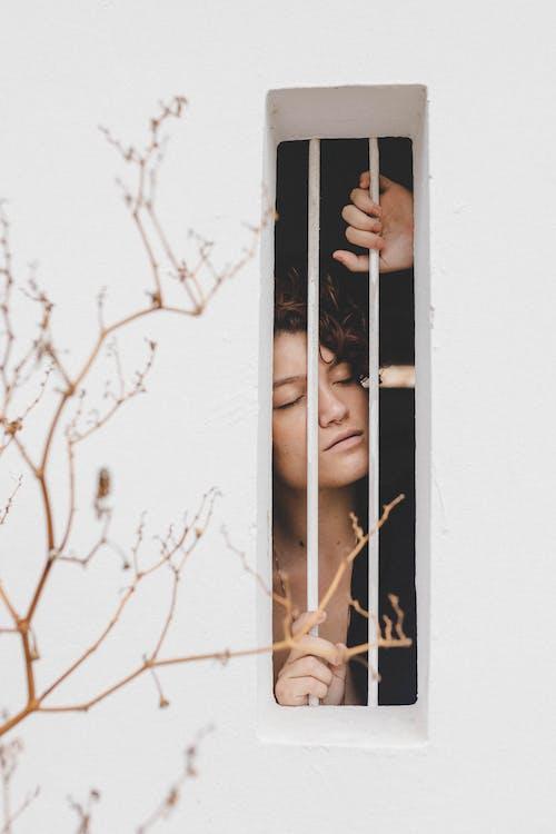 Woman in Black Shirt Standing Beside White Wooden Window