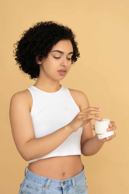 Woman in White Tank Top Holding A  Beauty Cream