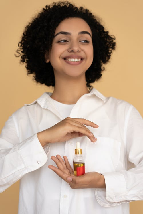 Woman in White Dress Shirt Holding a Bottle