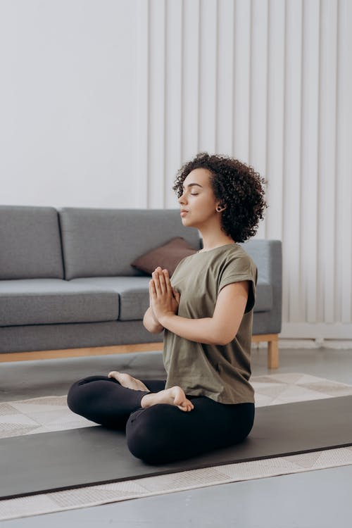 Woman in Brown T-shirt and Black Pants Sitting on Floor In Yoga Position