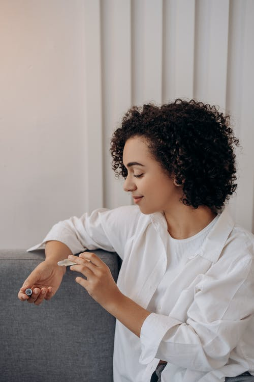 Woman in White Dress Shirt Trying An Essential Oil On Her Wrist