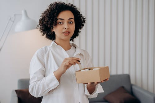 Woman in White Long Sleeve Shirt Holding A Box Of Essential Oils