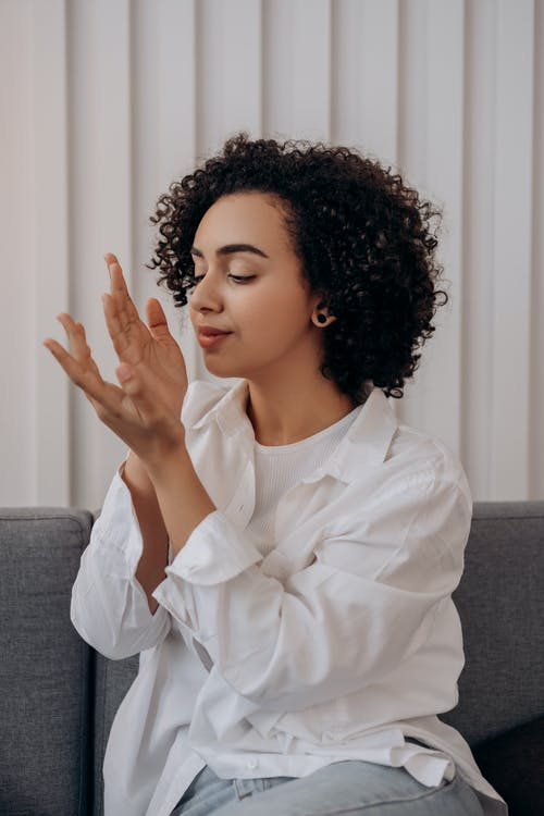 Woman in White Dress Shirt Smelling Her Hands