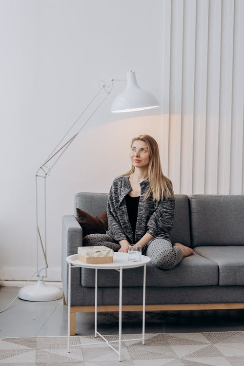 Woman Sitting on Gray Couch With Floor Lamp Beside Her