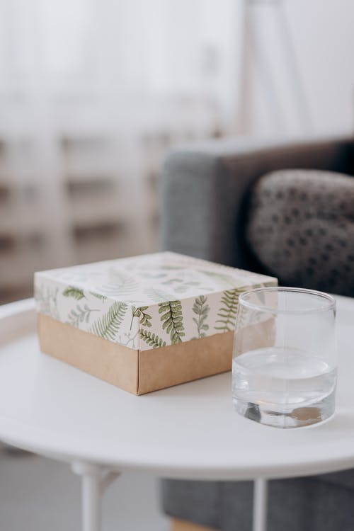 Box Of Essential Oils And Glass Of Water On Table