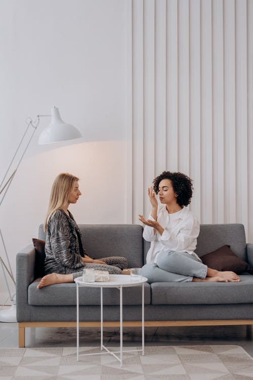 Two Women Sitting on Gray Couch