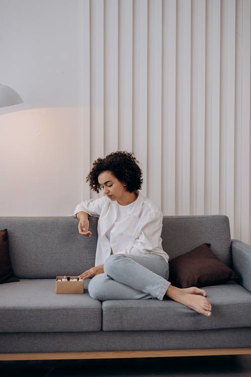 Woman in White Dress Shirt Sitting On A Couch With A Box Of Essential Oils