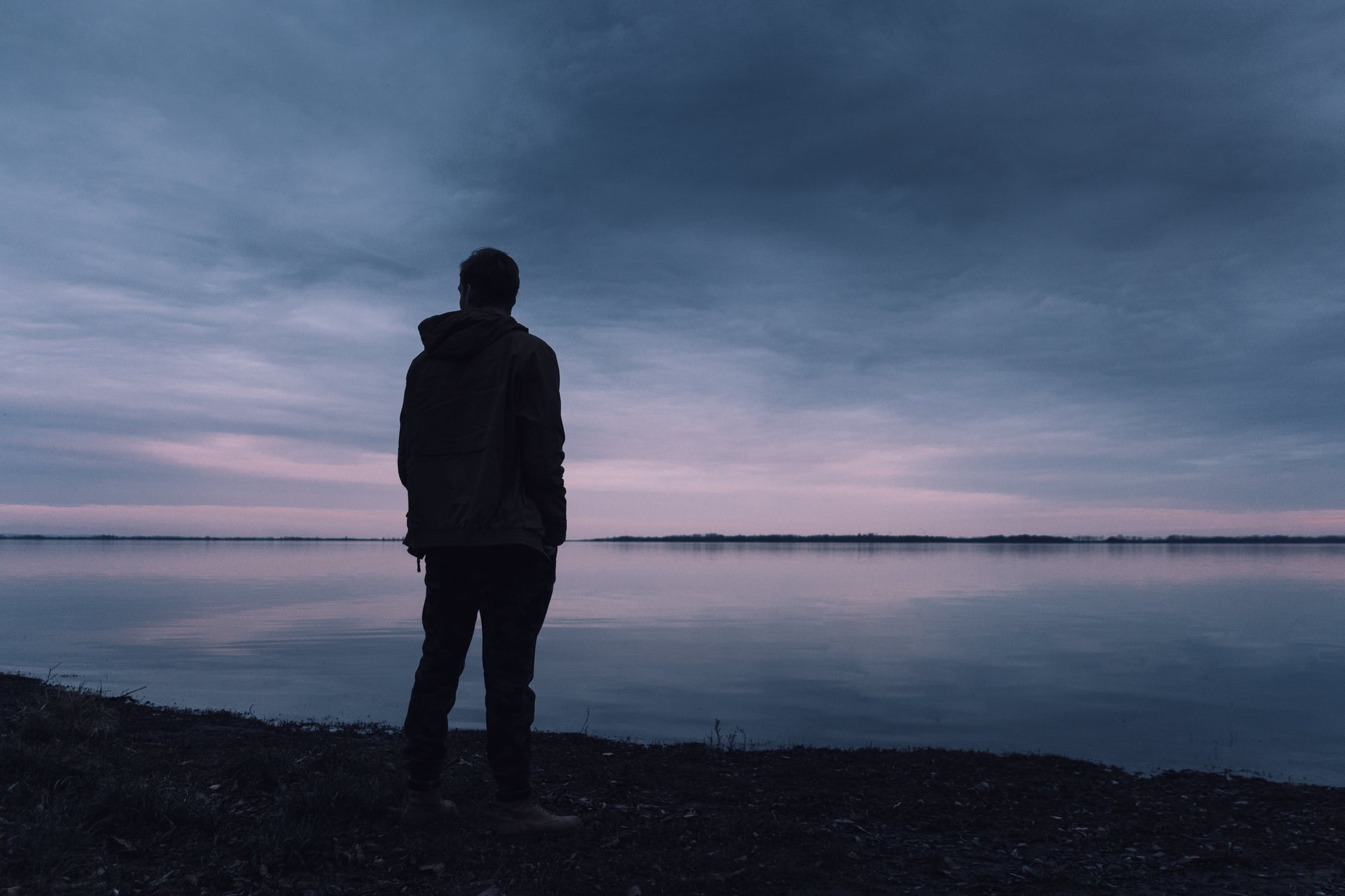A silhouette of a man looking across a vast lake. Photo by Lukas Rychvalsky. Used Courtesy of Pexels.comby