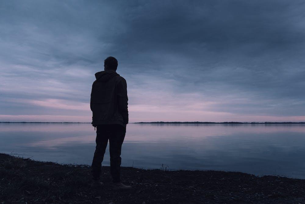Man looking at lake alone