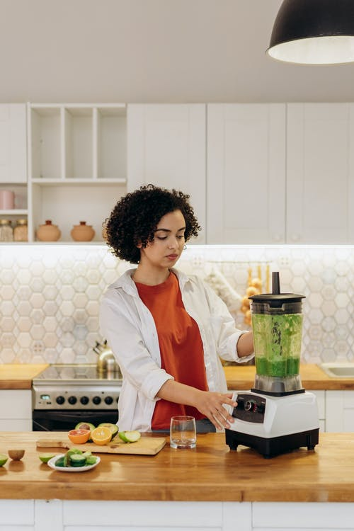 Woman in White Long Sleeve Shirt Making A Smoothie