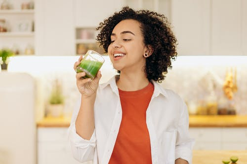 Woman in White Blazer Drinking A Fresh Smoothie