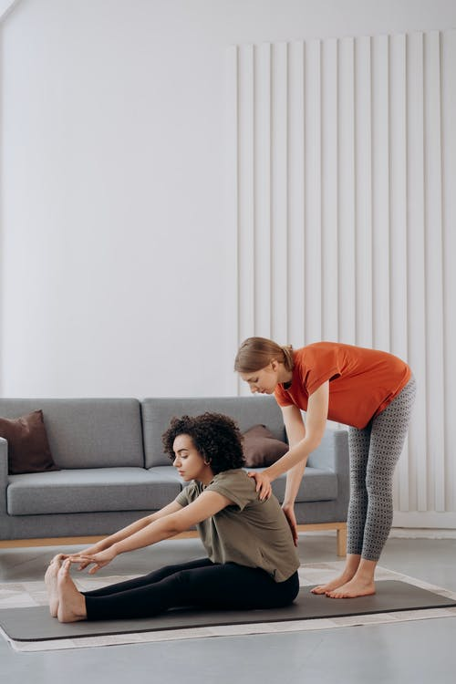Two Women Helping Each Other Doing Yoga
