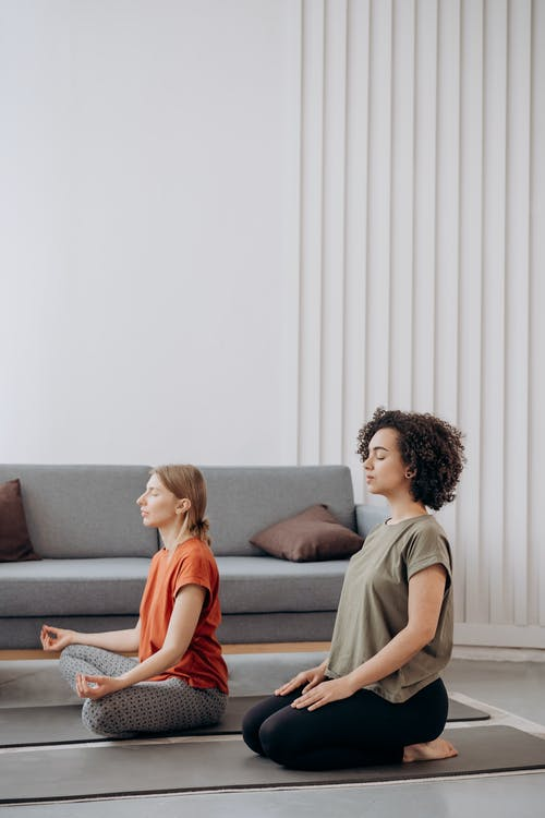 Two Women Sitting In A Yoga Position