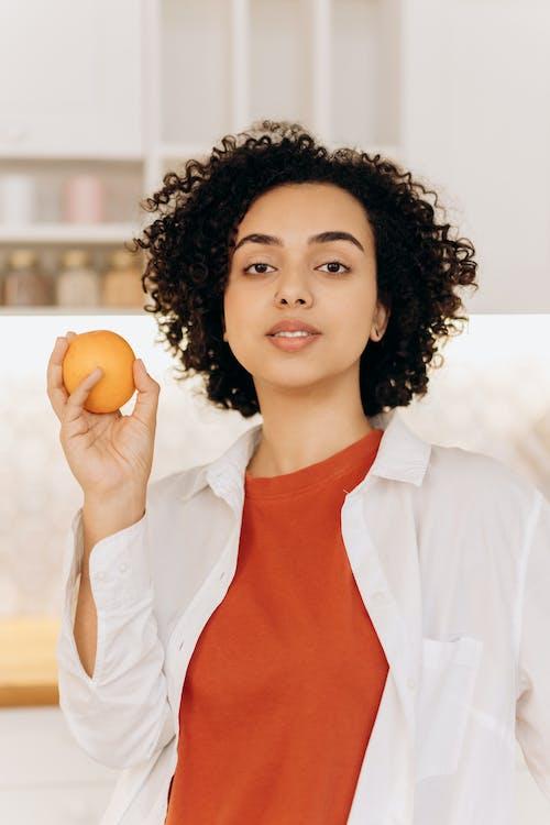 Girl in White Button Up Shirt Holding Orange Fruit