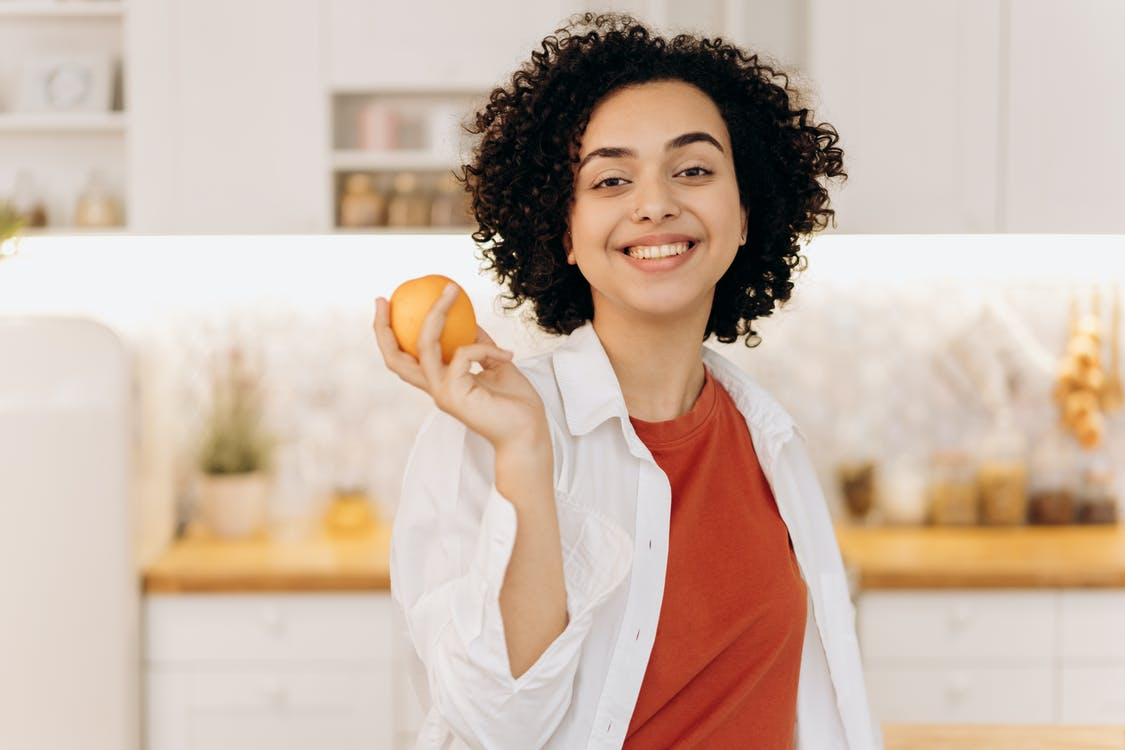 Woman in White Button Up Shirt Holding Orange Fruit