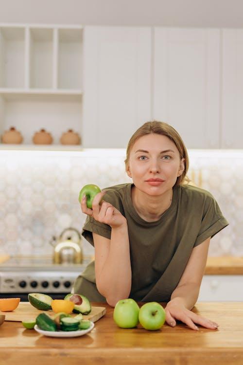 Smiling Girl in Green Crew Neck T-shirt Holding Green Apple Fruit