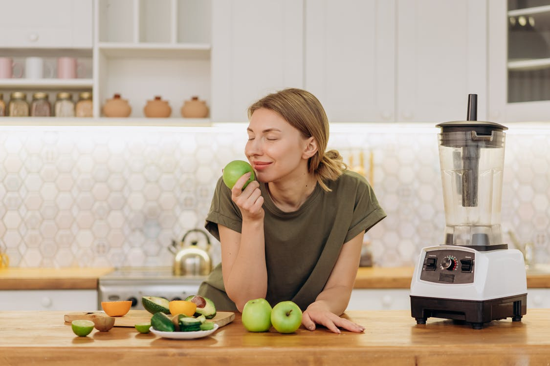 Satisfied Woman Smelling a Fruit