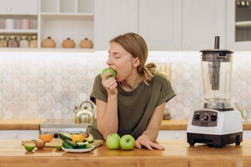 Woman in Gray Crew Neck T-shirt Eating Green Apple Fruit