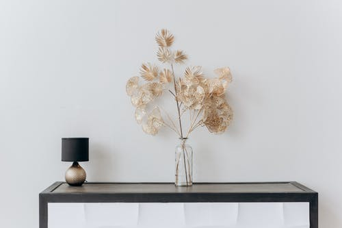Flower Vase And Lamp On Black Vase on A Console Table