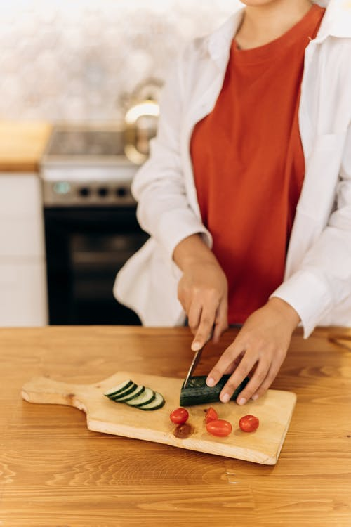 Woman Slicing A Cucumber