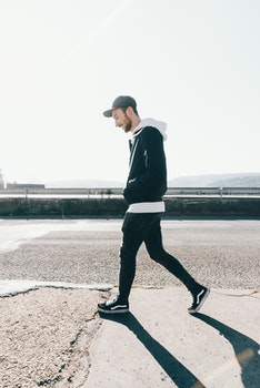 Man Walking on Road Under the Sun