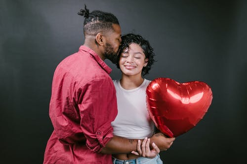 Man Kissing His Woman While Holding a Red Heart Shaped Balloon
