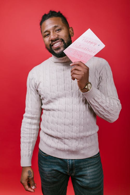 Man in White Sweater Holding a Valentine's Day Card