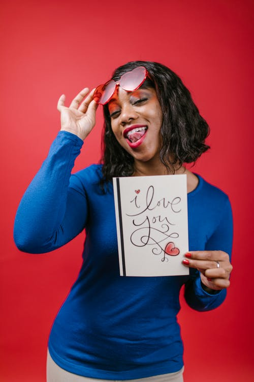 Woman in Blue Long Sleeve Shirt Holding Valentine's Day Card