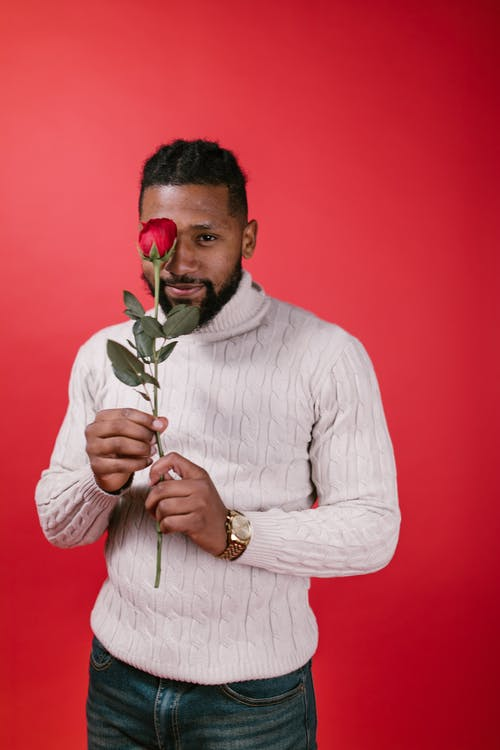 Man in White Sweater Holding Rose