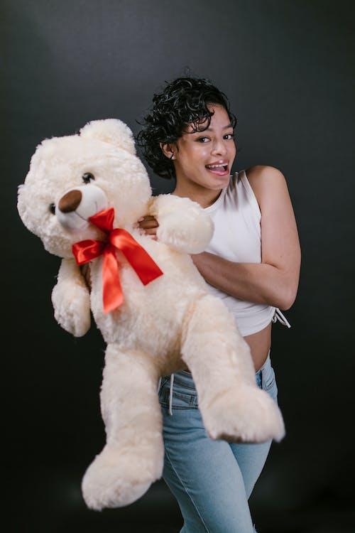 Woman in White Tank Top Holding White Bear Plush Toy