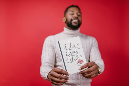 Man in White Long Sleeve Shirt Holding Valentine's Day Card