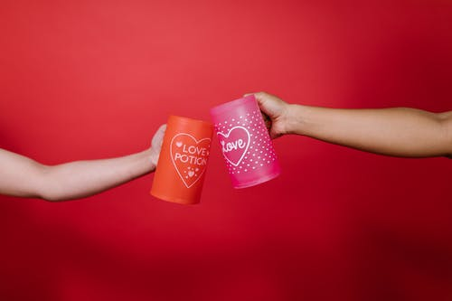 Two Person Holding Red and Pink Mug