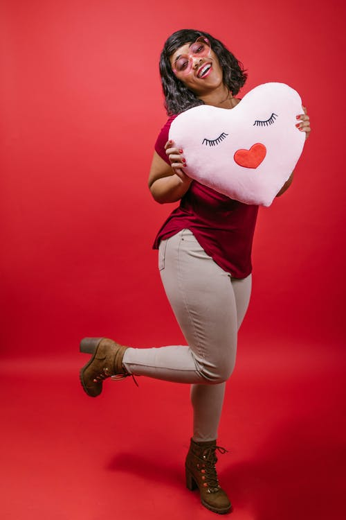 Woman Holding a Pink Heart Shaped Pillow