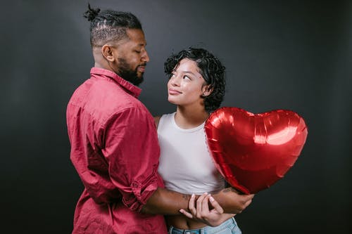 Couple Looking at Each Other While Holding a Red Heart Shaped Balloon