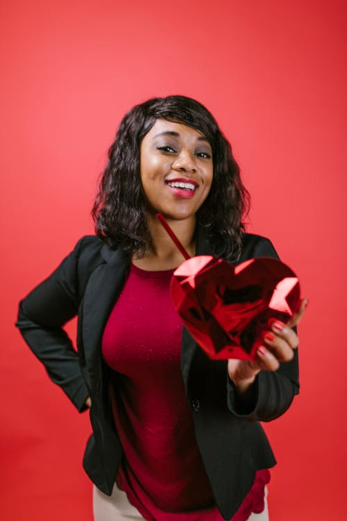 Woman Smiling While Holding a Red Heart Shaped Object