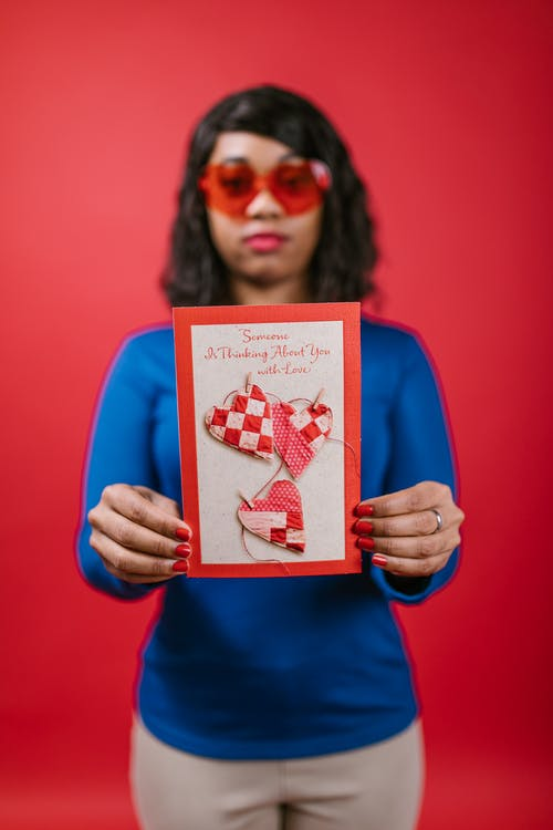 Woman in Blue Long Sleeve Shirt Holding Valentines Card