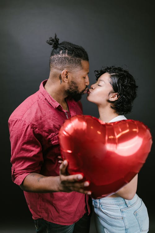 Couple Kissing While Holding a Red Heart Shaped Balloon