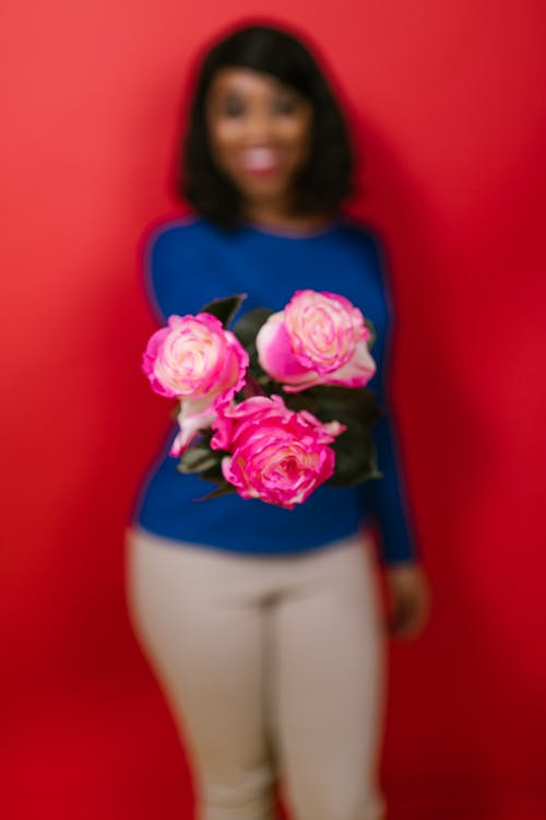 Shallow Focus of a Woman Holding Pink Roses