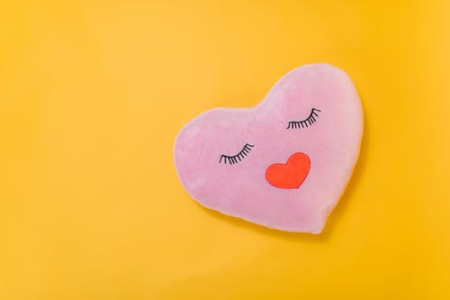 Pink Heart Shaped Pillow on Yellow Surface