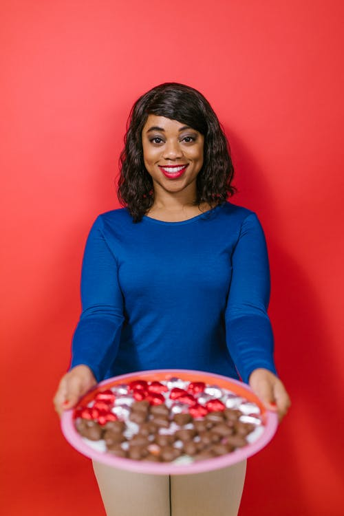 Woman in Blue Long Sleeve Shirt Holding a Plate of Chocolates
