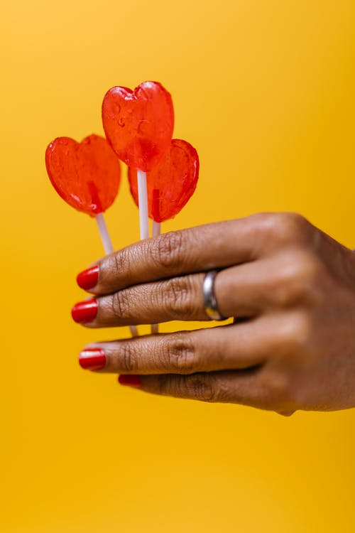 Person Holding Red Heart Shaped Lollipops