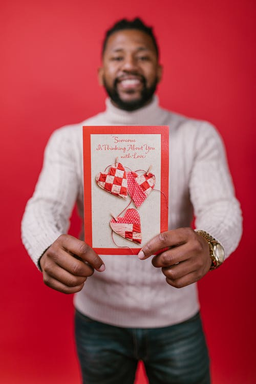 Man in White Long Sleeve Shirt Holding a Valentines Card