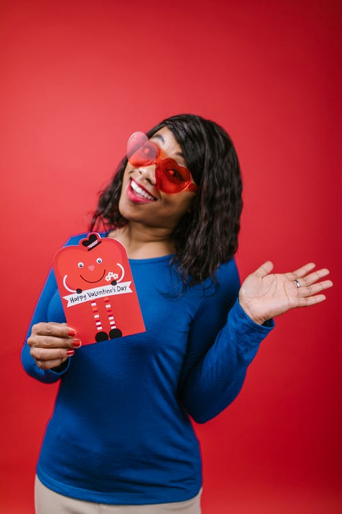 Woman in Blue Long Sleeve Shirt Holding a Valentines Card