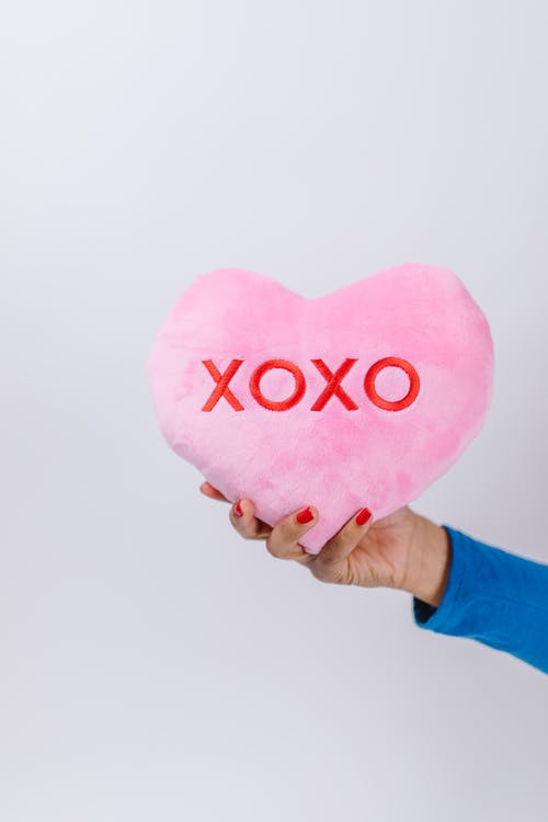 Person Holding Pink Heart Pillow
