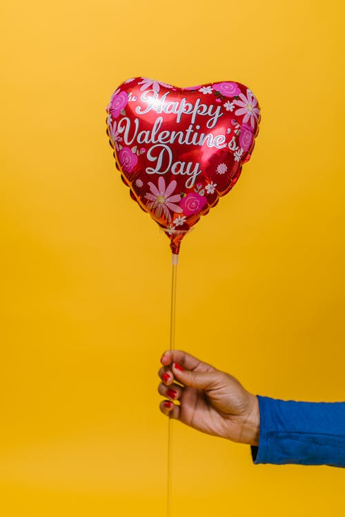 Person Holding a Red Heart Shaped Balloon
