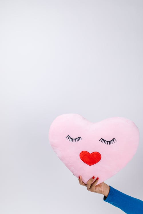 Person Holding Pink Heart Shaped Pillow