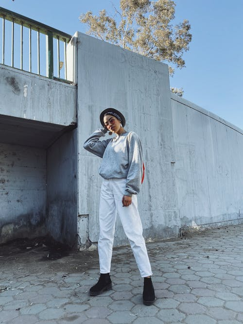 Stylish black woman standing on paved sidewalk and touching hat