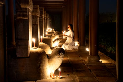 Side view of tranquil Asian female with burning candle in hands praying near stone turtles with steles in dark time