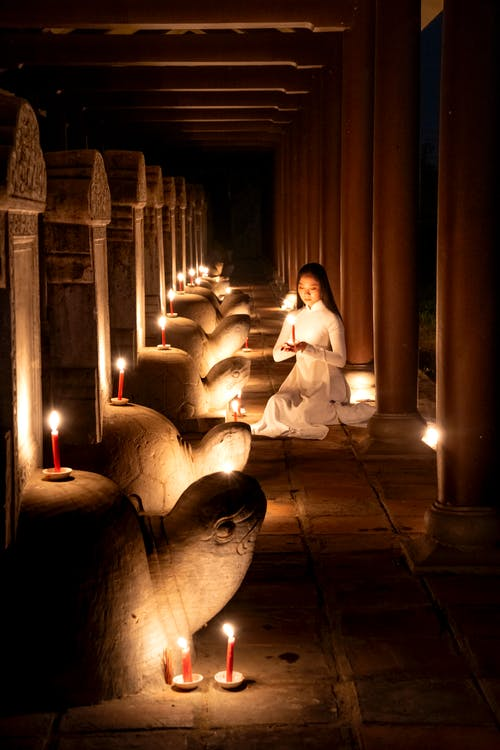 Calm Asian woman sitting on floor near statues with burning candles in dark temple