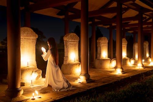 Woman praying in temple in night time